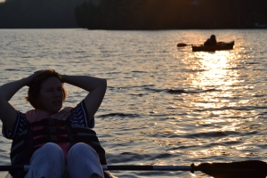 Girl in kayak at sunset