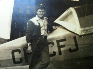 Young man in the 1930s standing in front of an airplane