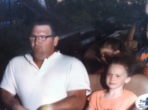 Father and daughter riding rollercoaster