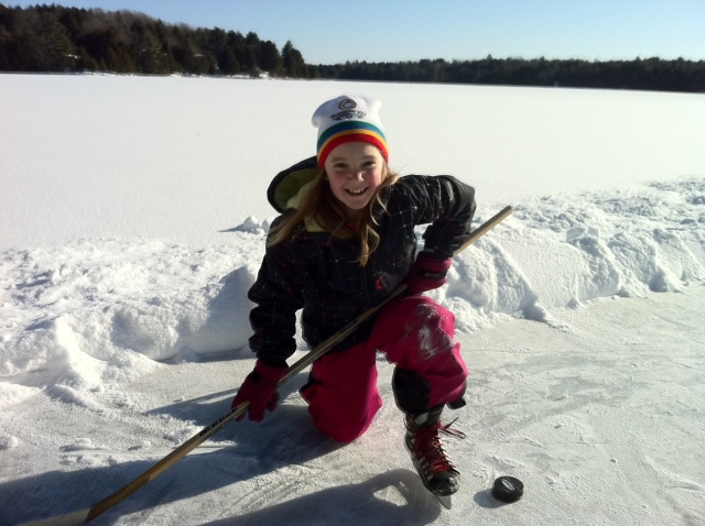 girl with hockey stick on frozen rink