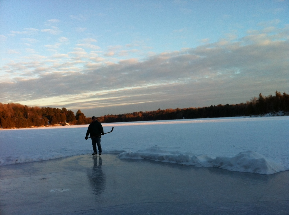 Man standing with hockey stick on a rink on a lake