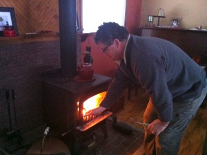Man lighting wood stove