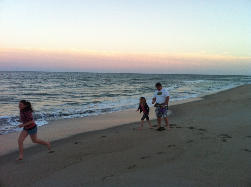 man and children playing on beach at sunset