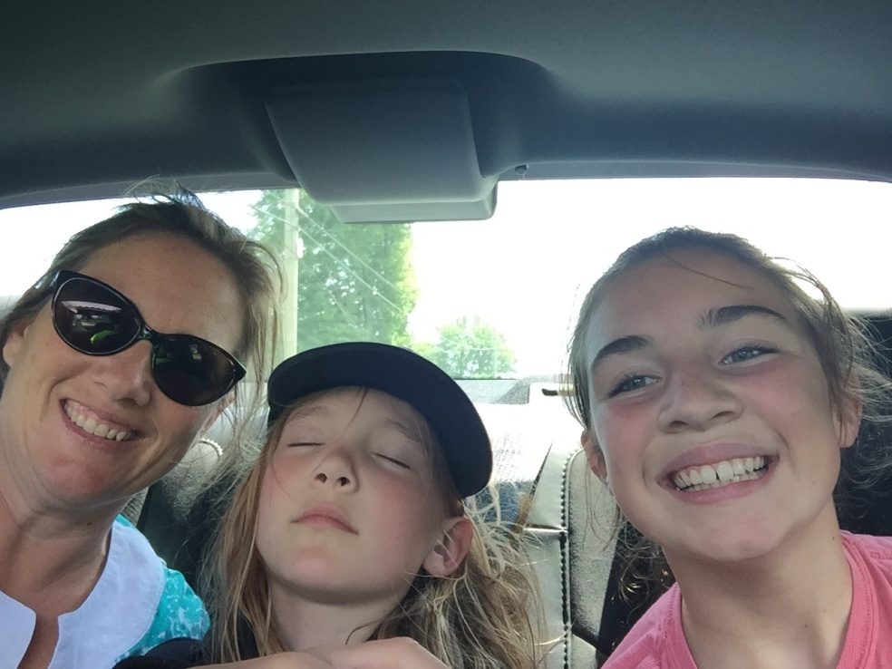 Three girls in the backseat of a car
