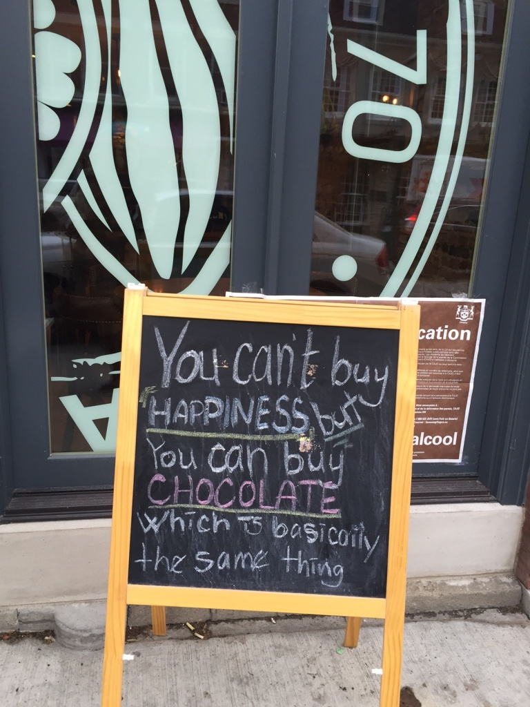 sign that says you can't buy happiness but you can buy chocolate which is basically the same thing
