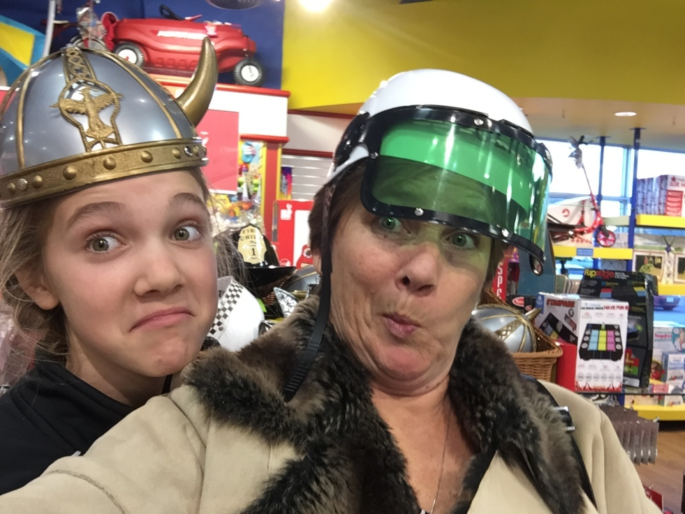 Girl and mother in funny hats in toy store
